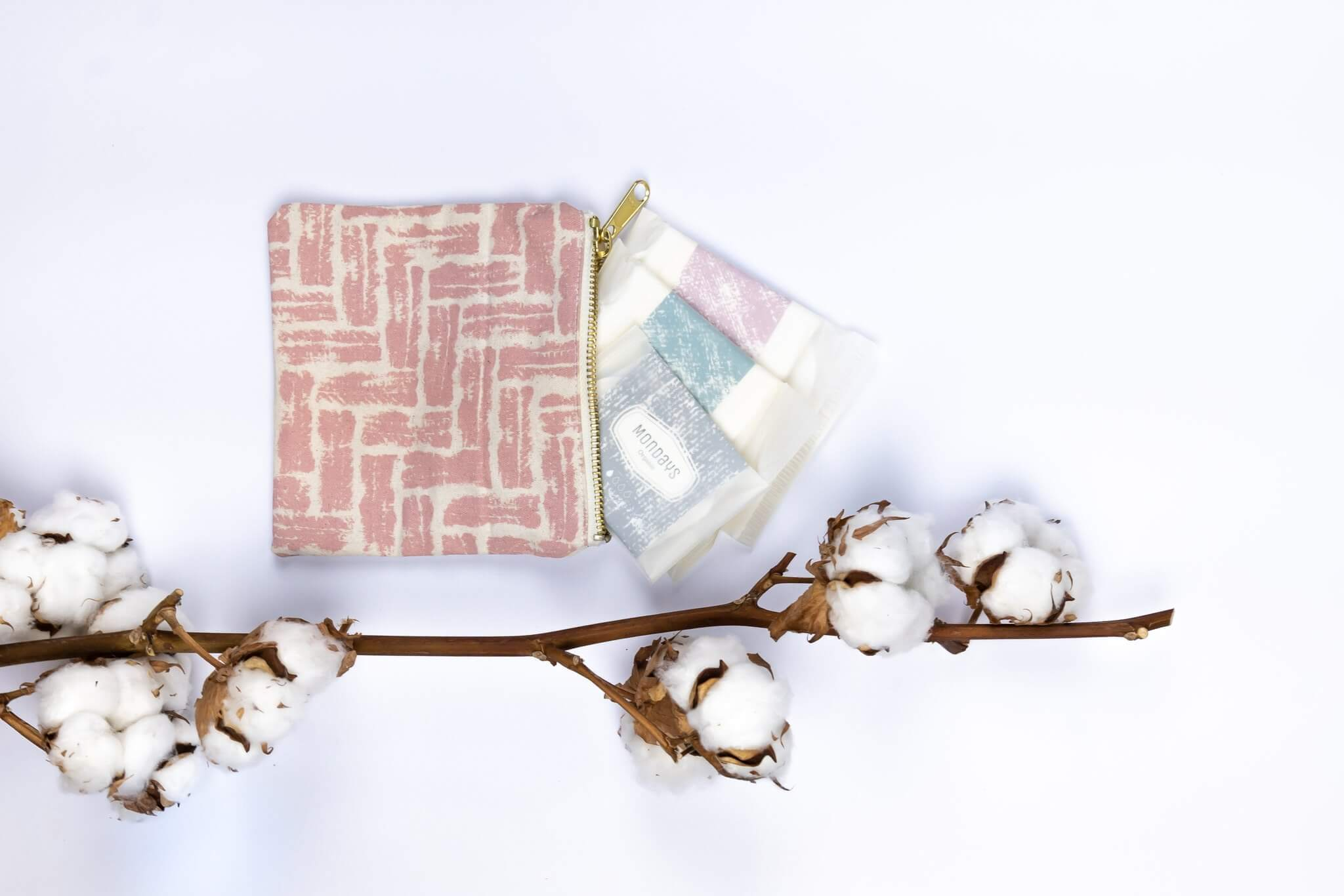 Organic Mondays eco friendly female hygiene products pictured against a white backdrop with a branch of cotton.