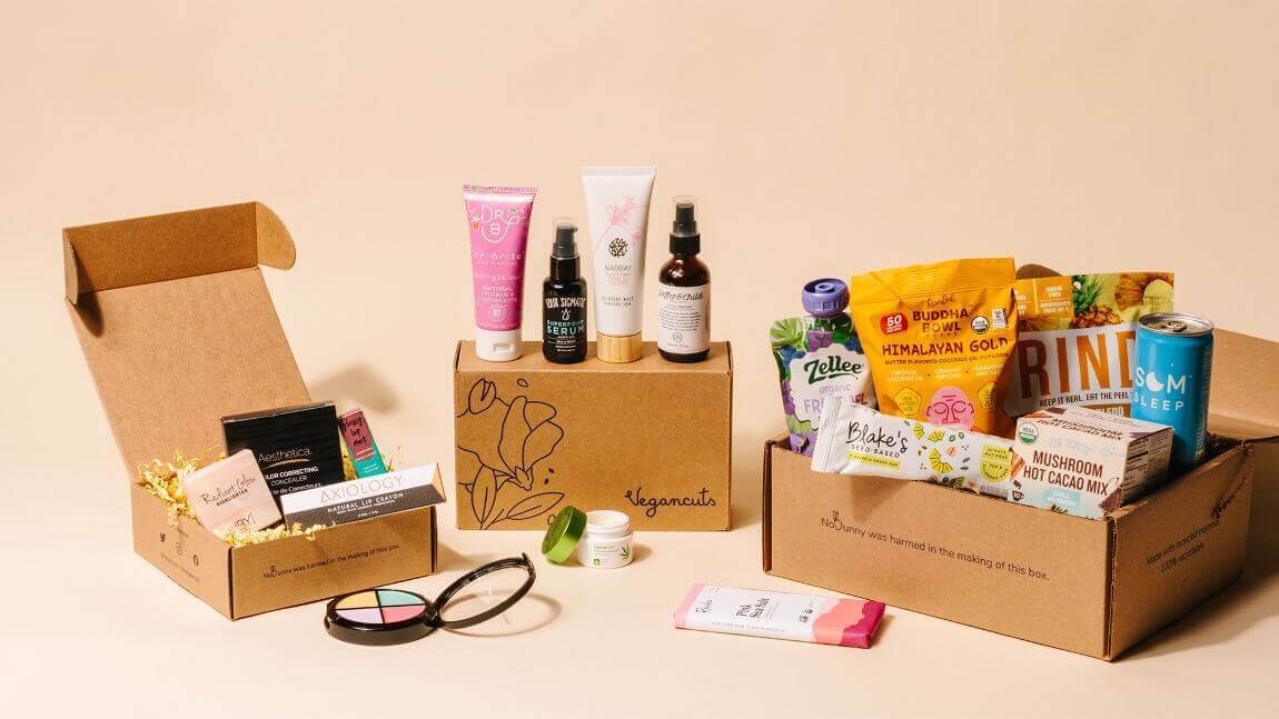 Three Vegancut subscription boxes arranged with an array of products, pictured against a pink backdrop.