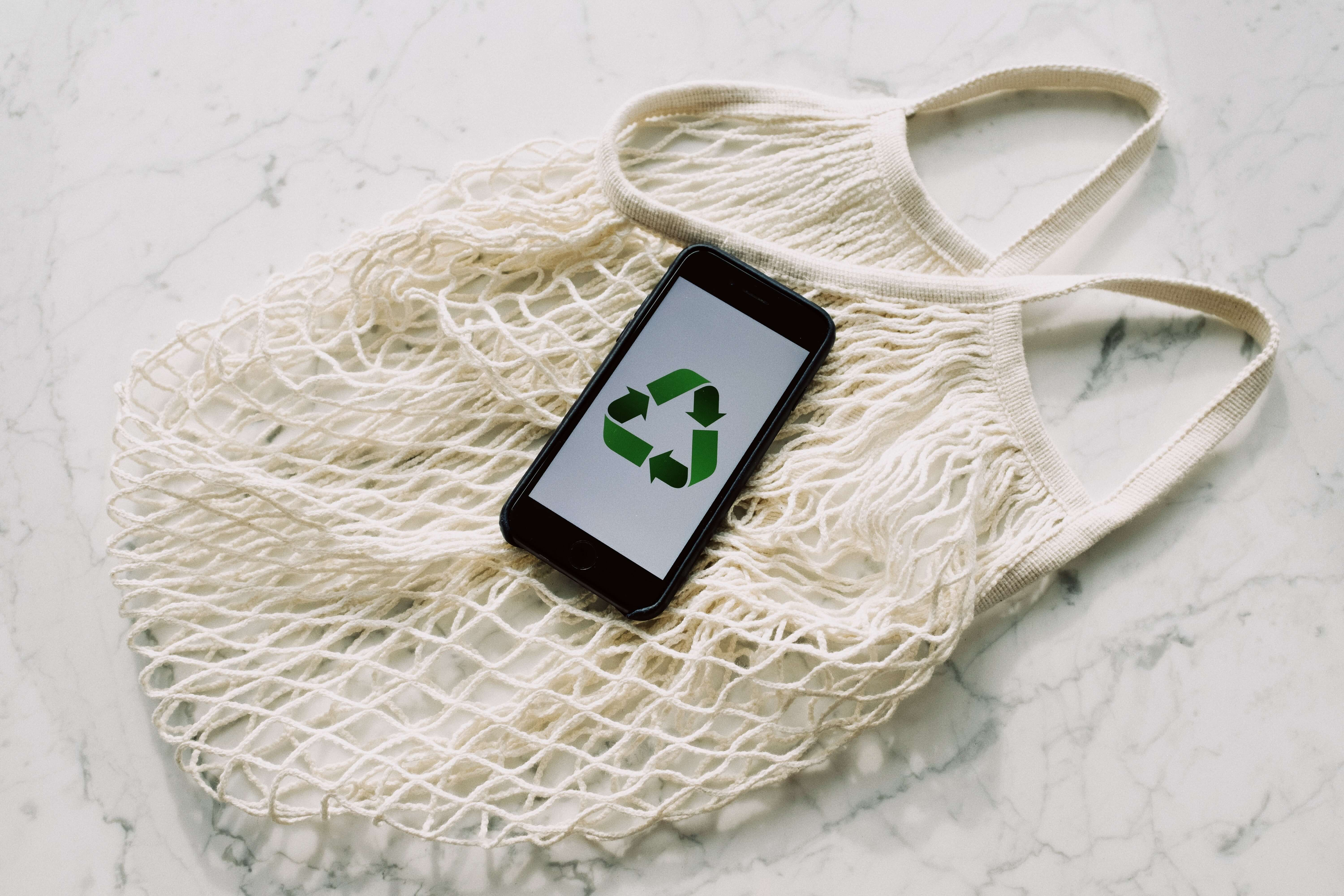 A sustainable mesh shopping bag with a phone on top of it that's displaying the recycle icon.