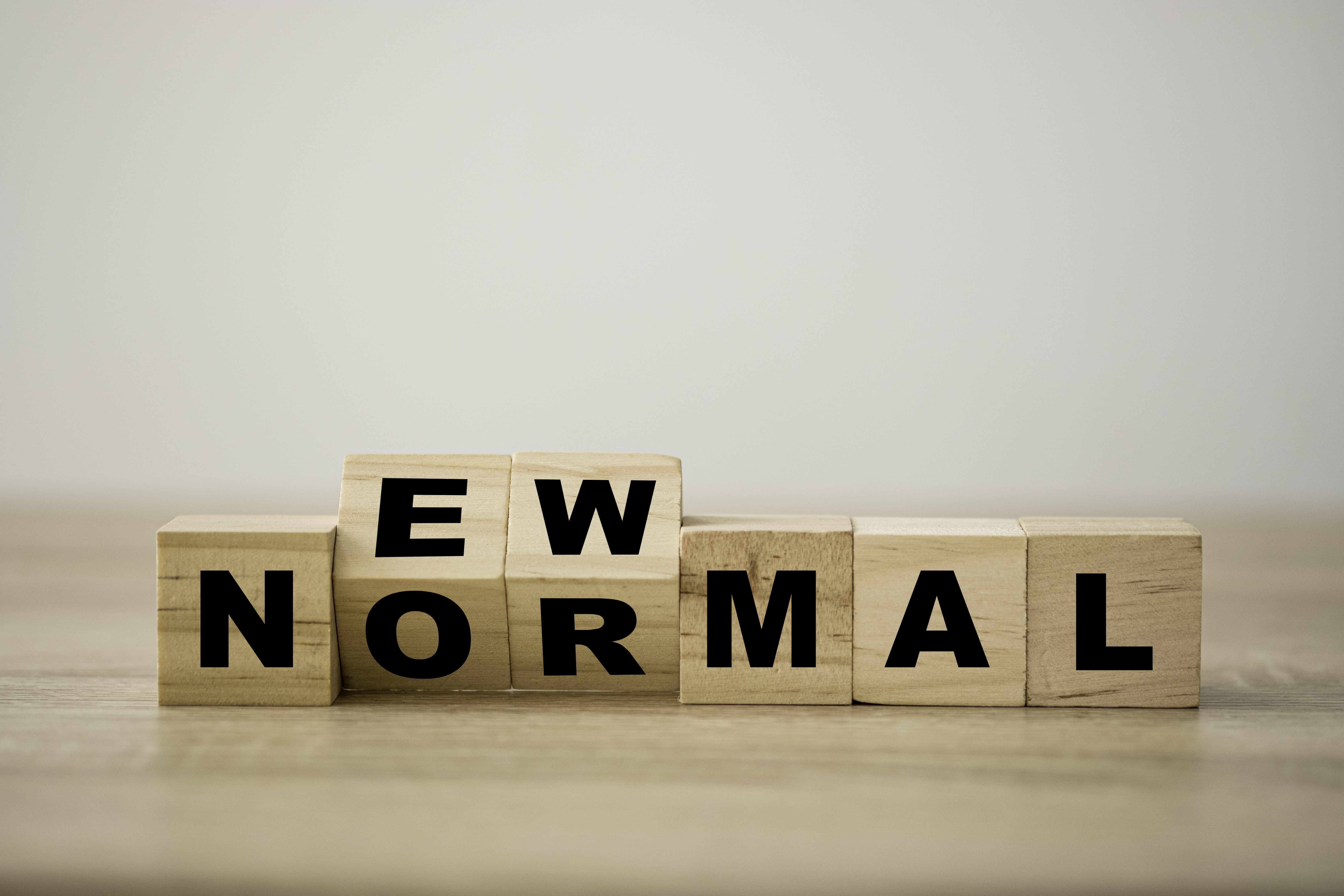Lettered wooden cubes that spell out a wordplay on 'normal' and 'new normal'.