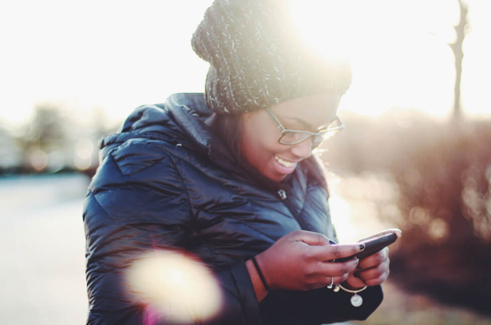 A woman on her phone, smiling.