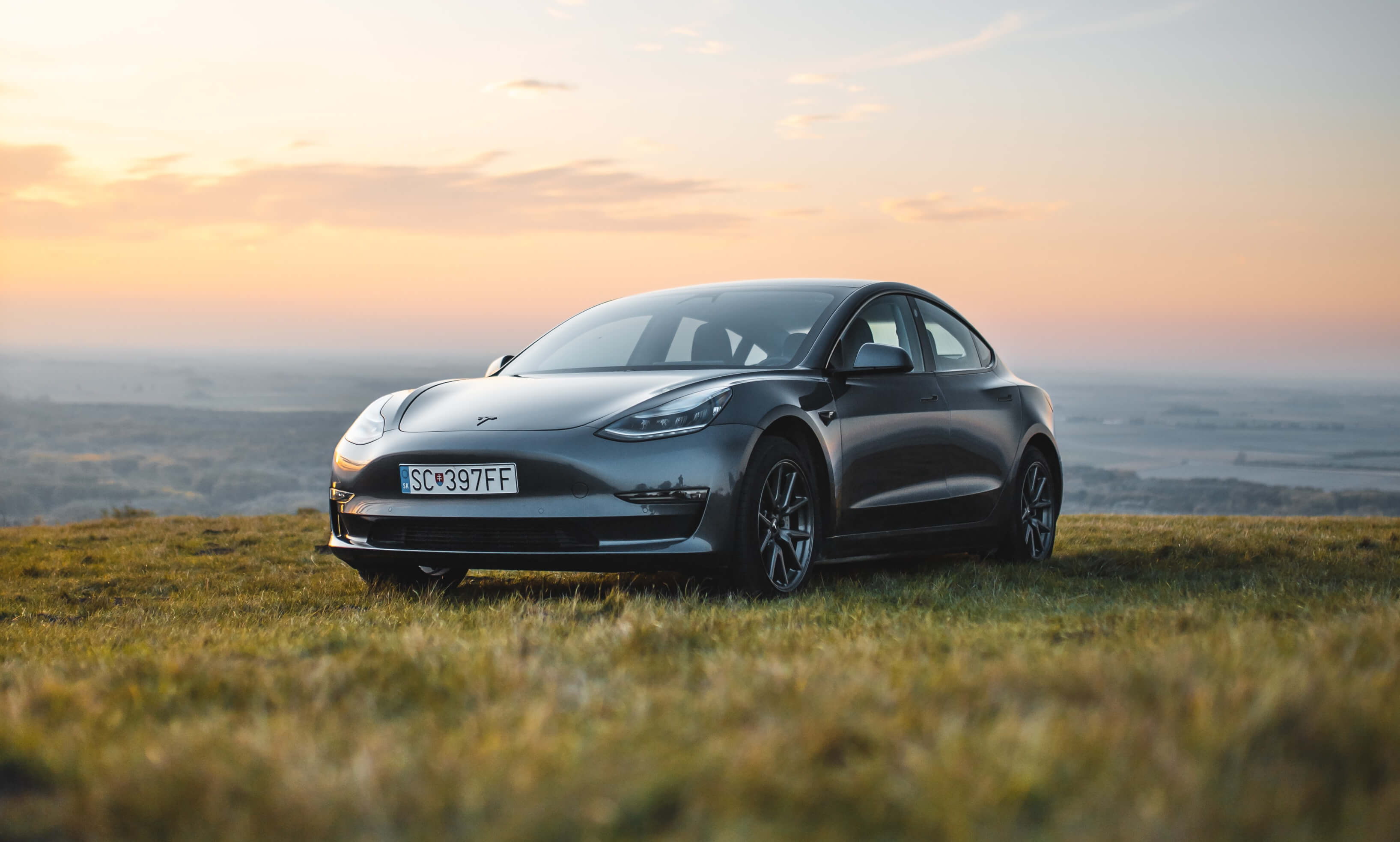 A Tesla car majestically perched on a hill at sunset.